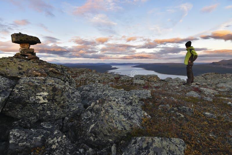 Le randonneur masculin accompli appréciant le coucher du soleil a coloré le paysage après audace jusqu'au dessus de montagne photos libres de droits