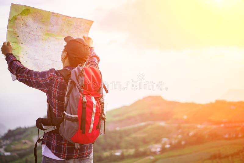 Le randonneur perdu avec le sac à dos vérifie la carte pour trouver des directions photo libre de droits