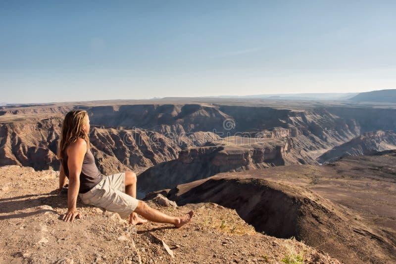 Le randonneur regarde le canyon de rivière de poissons photographie stock libre de droits