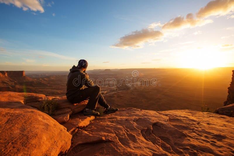 Le randonneur rencontre le coucher du soleil au point de vue grand dans le ressortissant de Canyonlands image stock