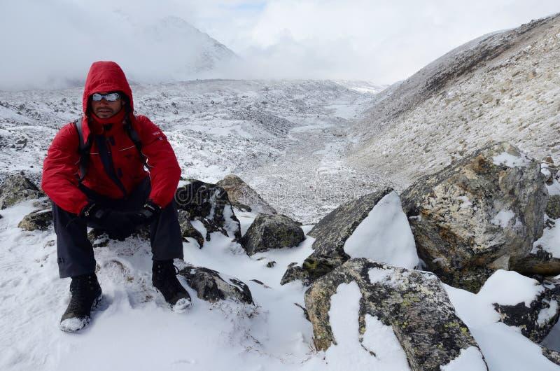Le randonneur s'est habillé dans le manteau rouge et les lunettes de polarisation se reposant sur son chemin au camp de base d'Ev images libres de droits