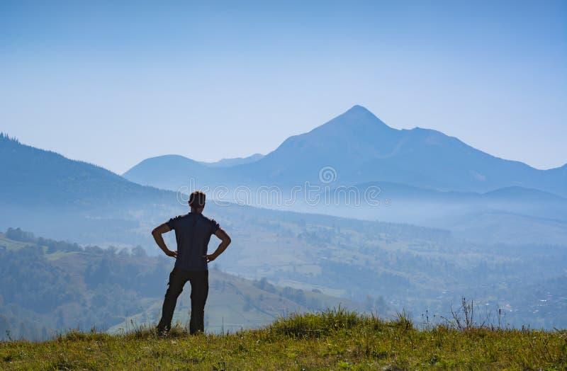 Le randonneur se tenant sur une colline et apprécient l'arête de haute montagne images stock