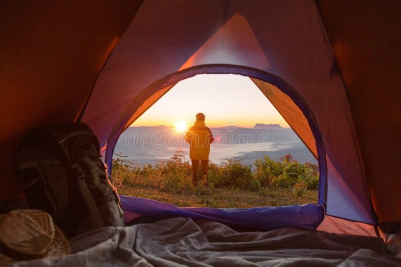Le randonneur se tient à la tente campante et au sac à dos oranges avant dans les montagnes photographie stock libre de droits