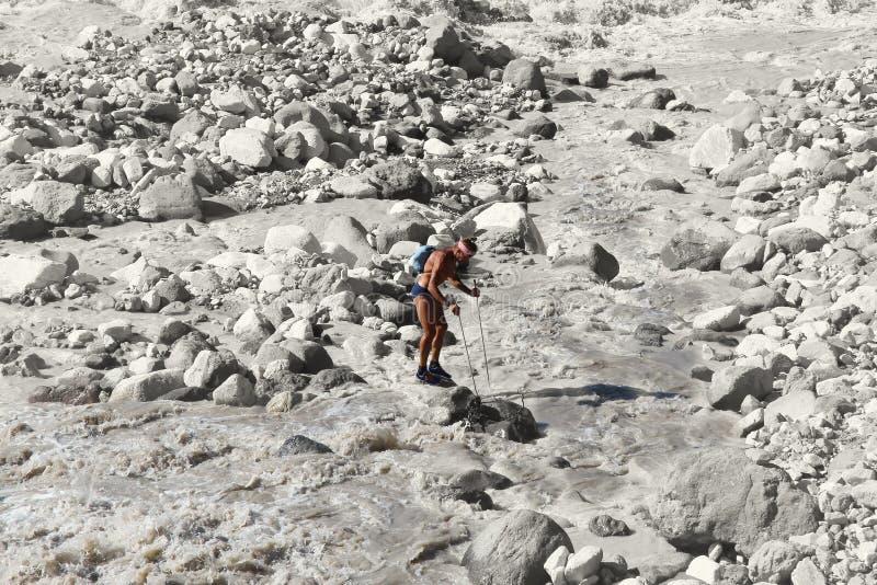 Le randonneur se tient sur une roche au beau milieu d'une rivière faisante rage de montagne images libres de droits