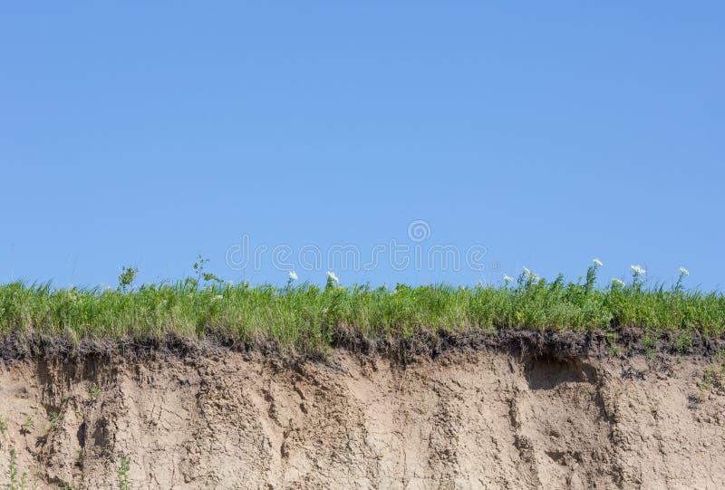 Le ravin ou le caniveau a coupé avec le sol, l'herbe et le ciel bleu photographie stock