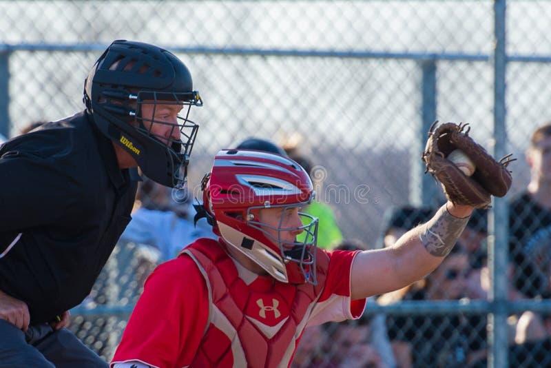 Le receveur de base-ball de lycée attrape le lancement photo stock