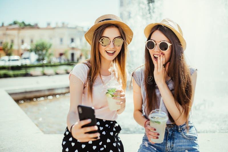 Le recreat femelle heureux de deux meilleurs amis ensemble contre la fontaine, regardent gaiement le téléphone intelligent modern images stock