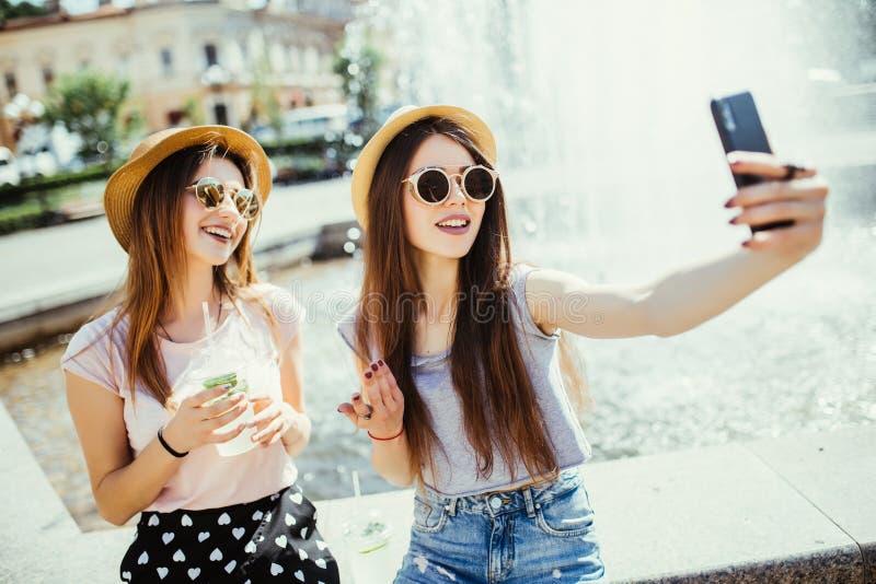 Le recreat femelle heureux de deux meilleurs amis ensemble contre la fontaine, regardent gaiement le téléphone intelligent modern photographie stock