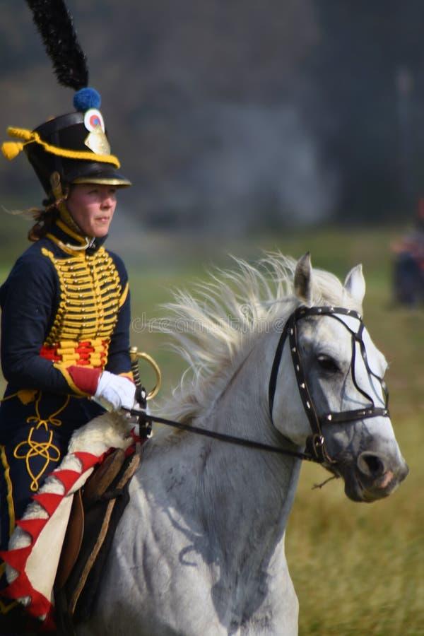 Le reenactor de femme monte un cheval à la reconstitution historique de bataille de Borodino en Russie photos stock