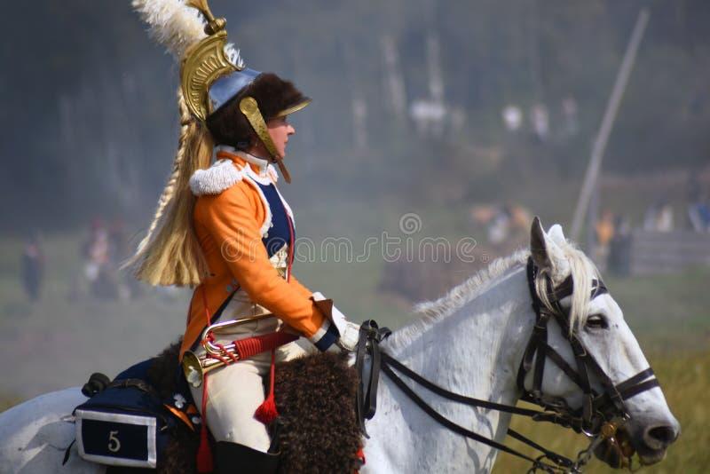 Le reenactor de femme monte un cheval à la reconstitution historique de bataille de Borodino en Russie image stock