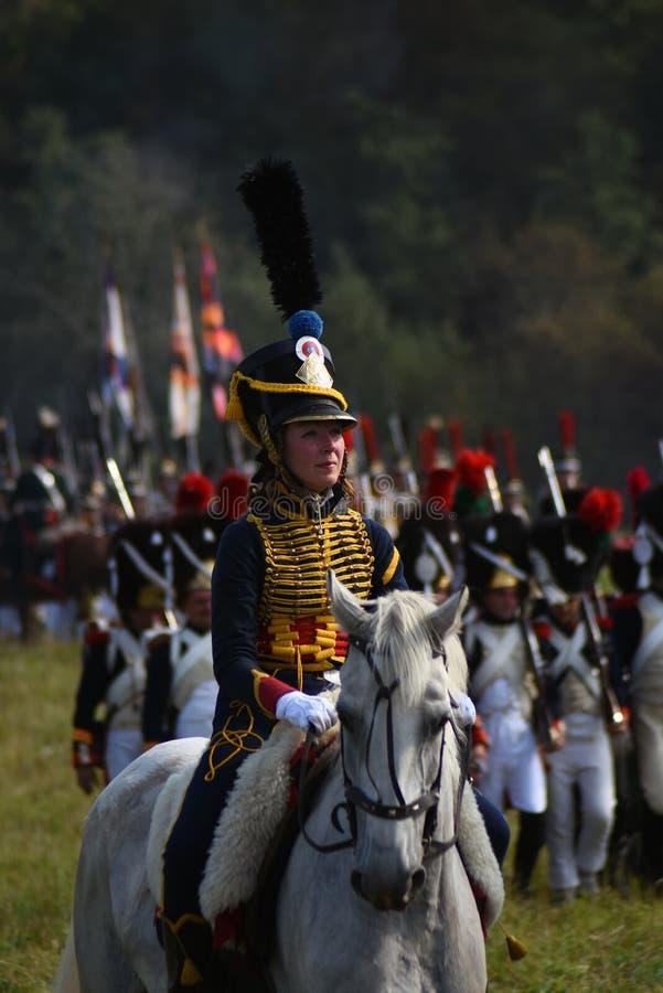 Le reenactor de femme monte un cheval à la reconstitution historique de bataille de Borodino en Russie images stock