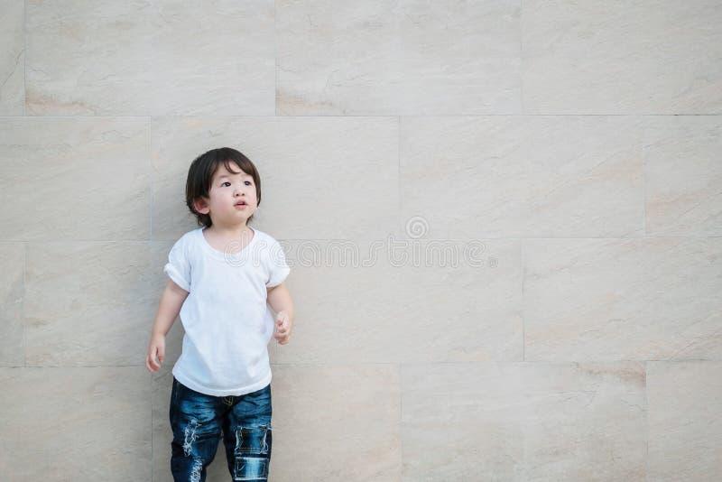 Le regard asiatique mignon d'enfant de plan rapproché à l'espace sur le mur en pierre de marbre a donné au fond une consistance r image libre de droits