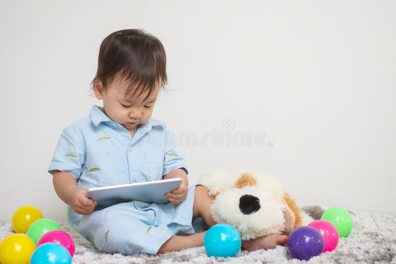 Le regard asiatique mignon d'enfant de plan rapproché au comprimé à la maison sur le tapis gris avec la poupée et le mur coloré d image libre de droits