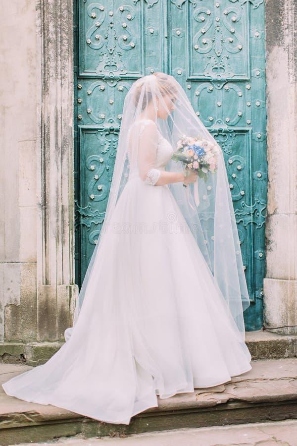 Le regard de la jeune mariée élégante avec le bouquet sous le voile photographie stock