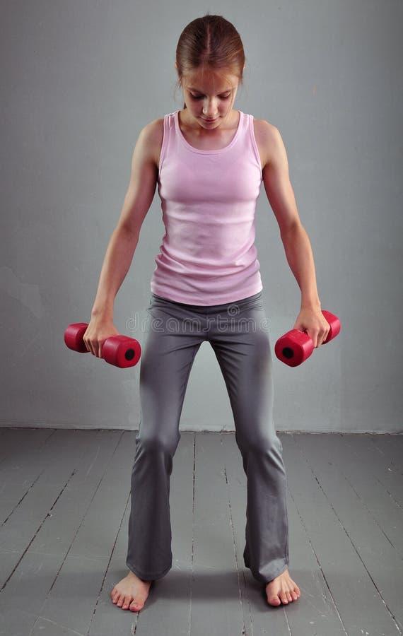 Le regard en bas de la fille folâtre adolescente fait des exercices pour développer des muscles d'isolement sur le fond gris Mode images libres de droits