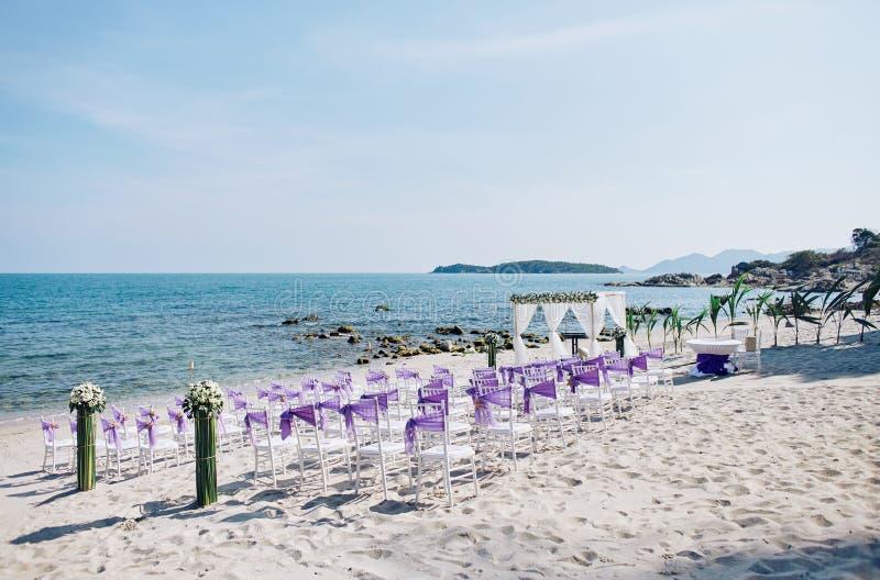 Le regolazioni della sede di nozze di spiaggia con le sedie bianche di chiavari decorano con il telaio porpora dell'organza alla  fotografia stock