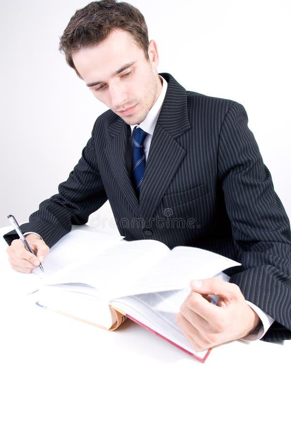 Le relevé beau et écriture de jeune homme dans le bureau image stock