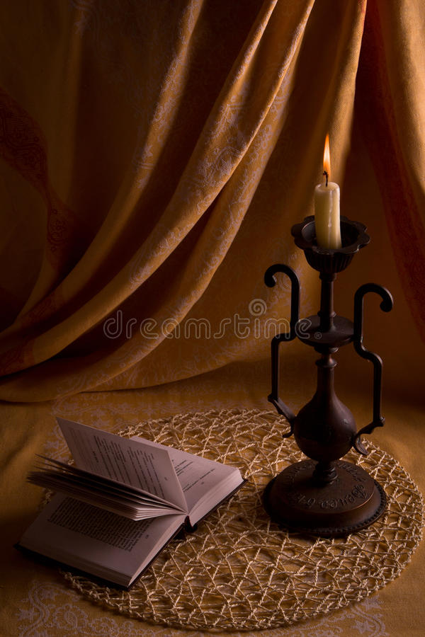Le relevé du livre par la lumière d'une bougie. photos libres de droits