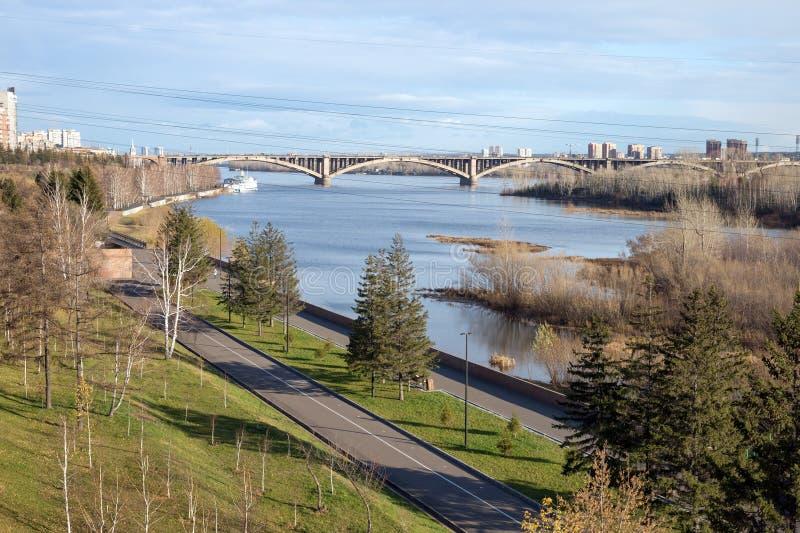Le remblai du fleuve Ienisseï et le pont communal d'automobile-piéton dans la distance dans la ville image libre de droits