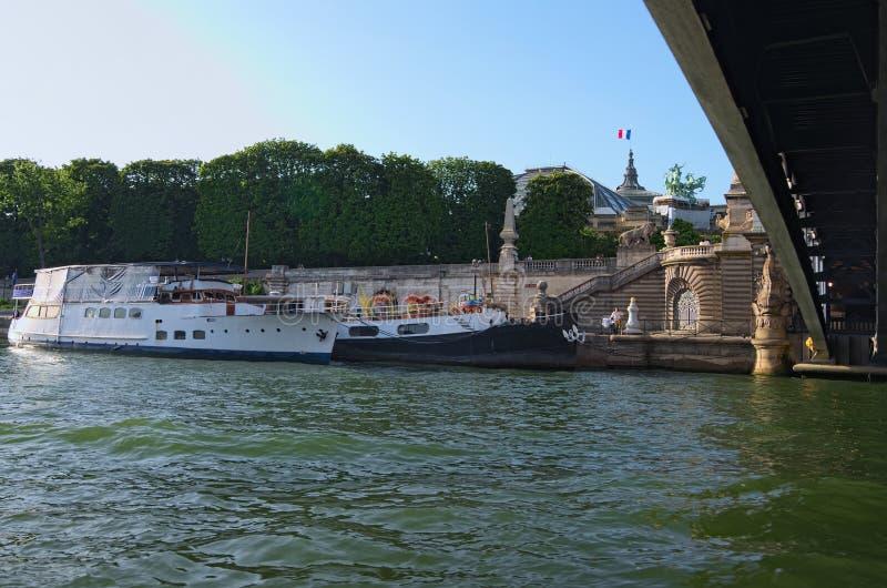 Le remblai pittoresque de la Seine avec la péniche résidentielle et les personnes de marche pendant le coucher du soleil Paris, F photographie stock
