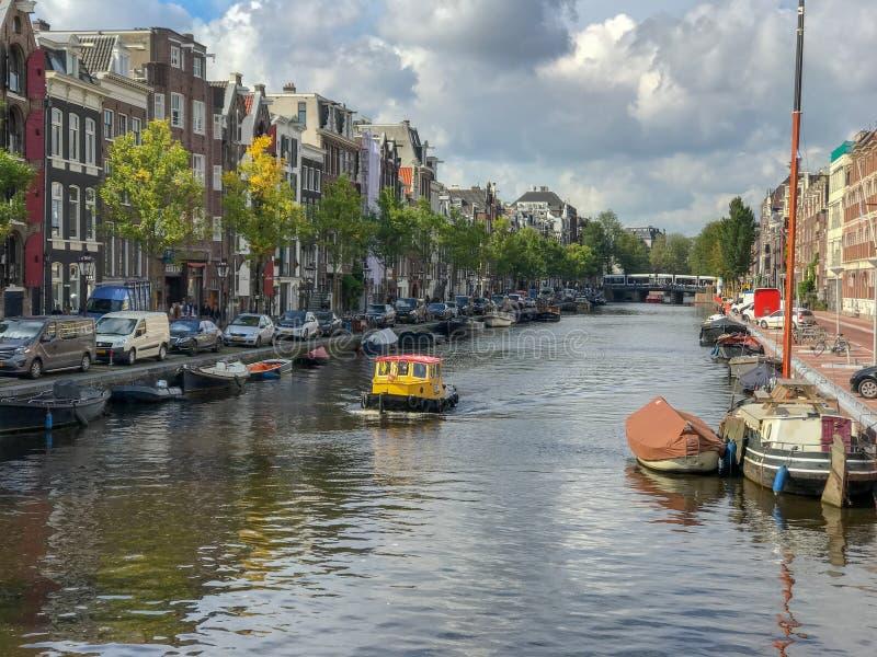 Le remorqueur jaune circule en voiture vers le haut du canal d'Amsterdam le jour nuageux de septembre photos libres de droits
