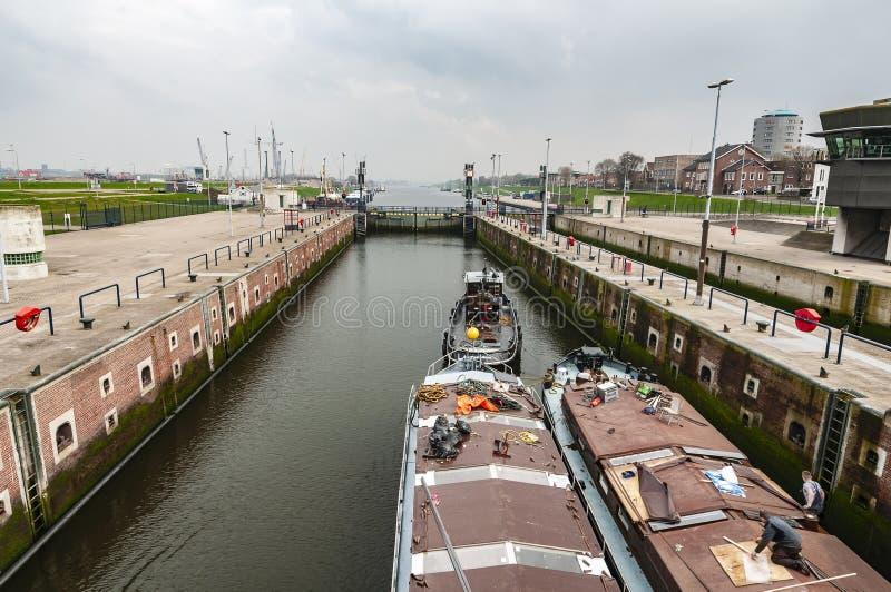 Le remorqueur remorque deux cargos par la petite serrure de la ville IJmuiden Pays-Bas images libres de droits