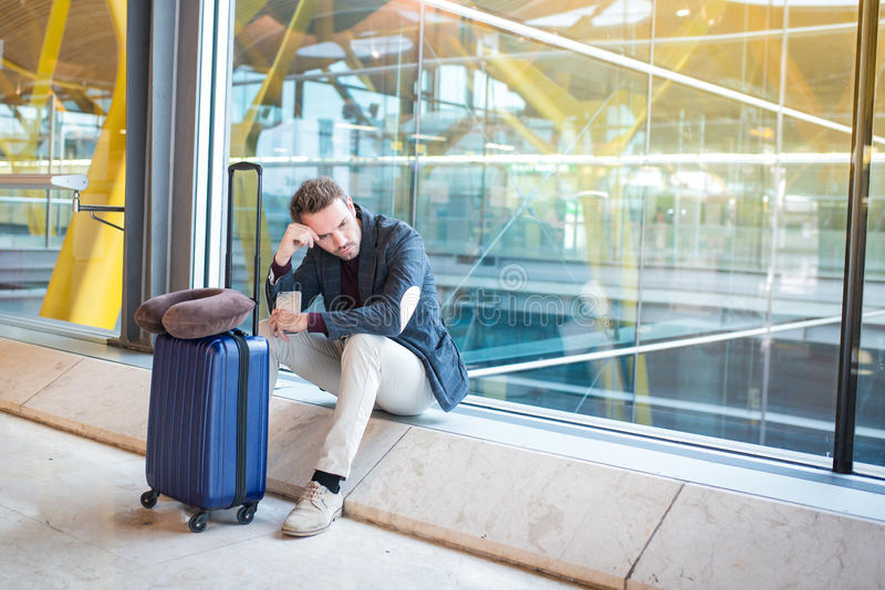 Le renversement d'homme, triste et fâché contre l'aéroport son vol est retardé photographie stock libre de droits