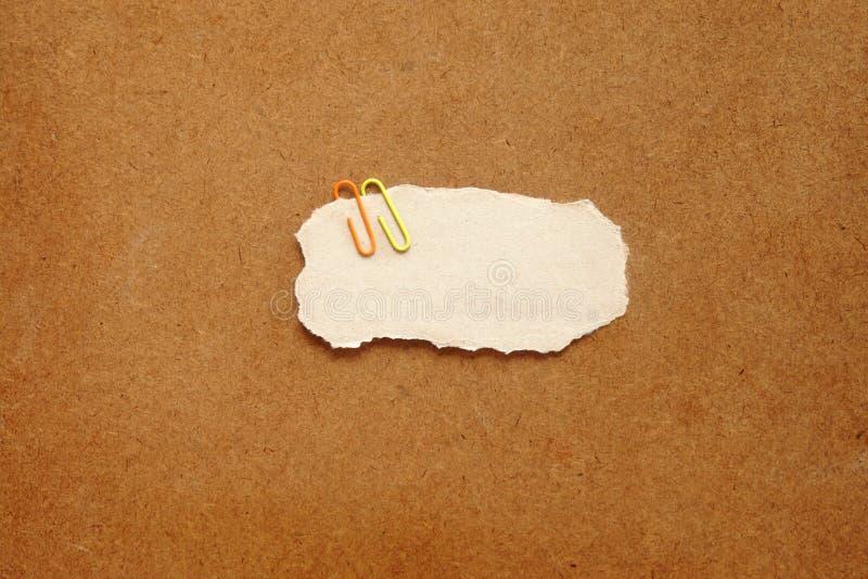 Le repli coloré d'agrafe en métal sur le papier brun de cercle ont l'espace de copie pour le texte mis sur le fond en bois de tab photos libres de droits