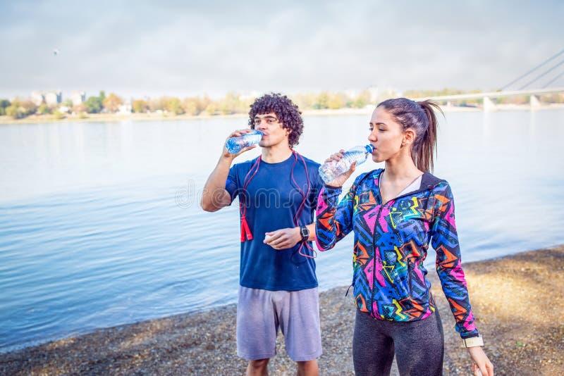 Le repos après des boissons de Séance d'entraînement-couples arrosent pour compléter le niveau de l'énergie photographie stock libre de droits