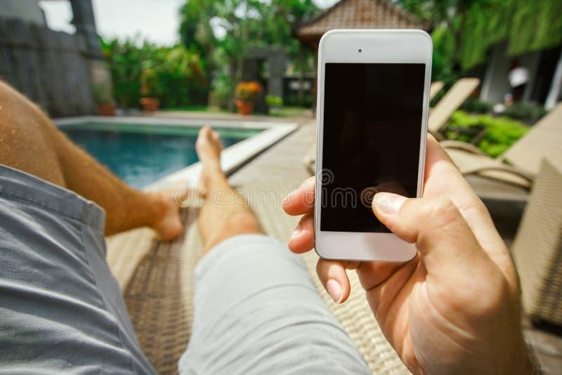 Le repos d'été détendent dans l'hôtel avec un téléphone à disposition Un homme se trouvant sur un canapé par la piscine et appréc photographie stock
