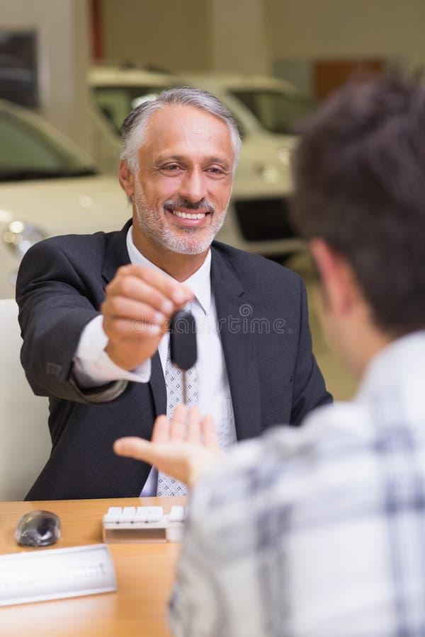 Le representanten som ger en kund biltangenter fotografering för bildbyråer
