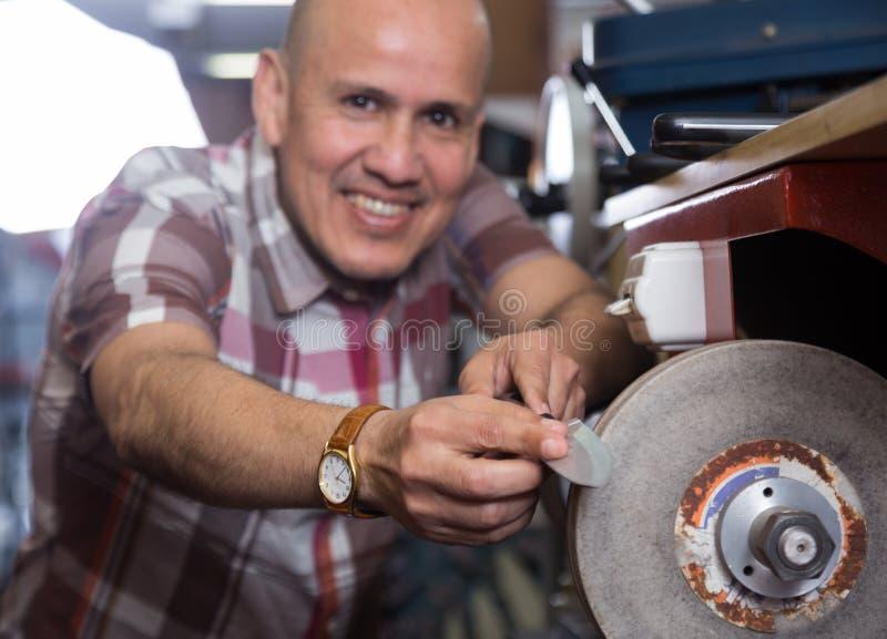 Le resharpering knivar för arbetare på det sy spiral hjulet för säkerthetsbrytare royaltyfri foto