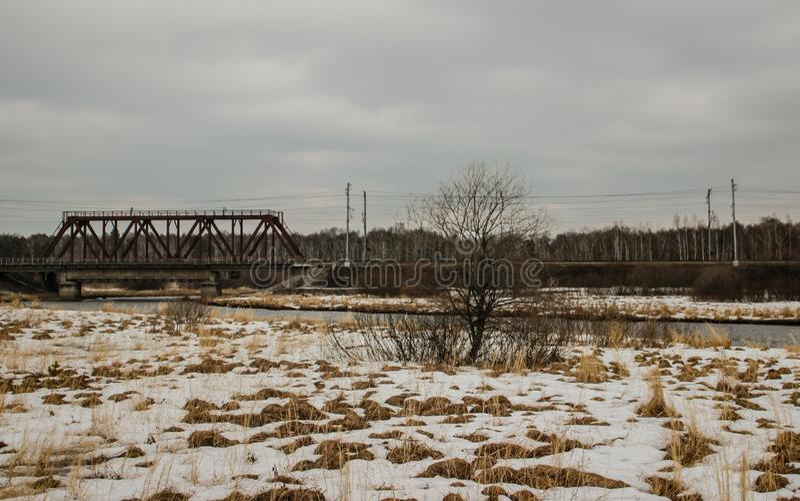 Le ressort, dans quelques endroits l? est neige, le pont de chemin de fer au-dessus de la rivi?re, le village image libre de droits
