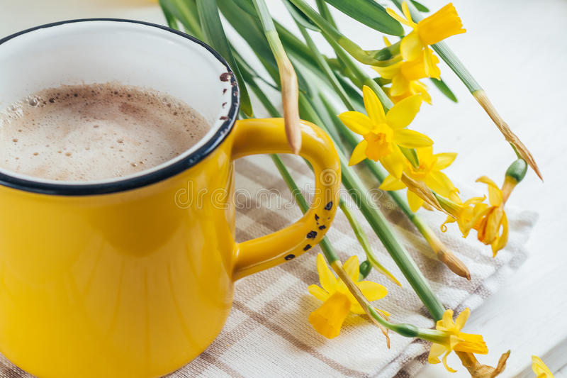 Le ressort fleurit des jonquilles avec une tasse de café, cappuccino, fin photographie stock libre de droits