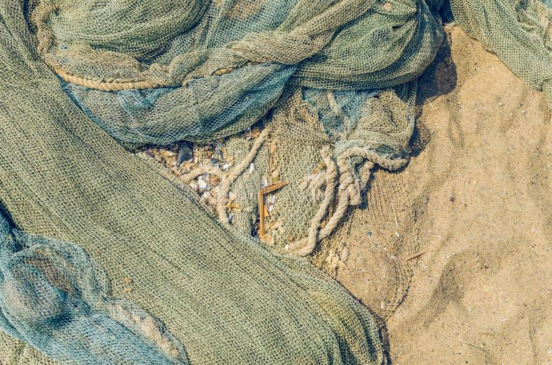 Le reti da pesca hanno piegato sulla spiaggia, struttura del fondo fotografie stock libere da diritti