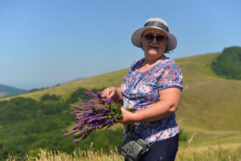 Le retraité de sourire actif de femme rassemble les fleurs sauvages dans les montagnes images stock
