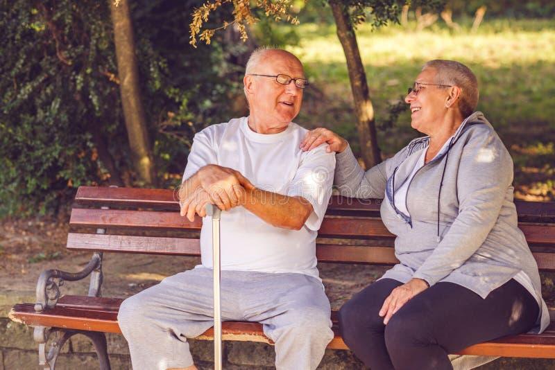 Le retraité de sourire couplent se reposer sur un banc de parc images libres de droits