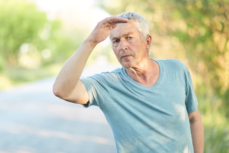 Le retraité masculin mûr sérieux beau garde la main près du front, examine la distance, essaye l'avis quelque chose, passe le tem photo libre de droits