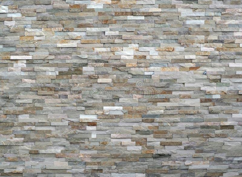 Le revêtement de mur en pierre fait de rayures empilées bascule Les couleurs sont de blanc au gris et au brun photos stock