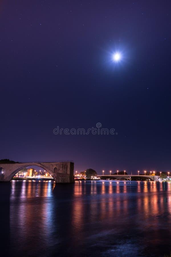 Le Rhône pendant la nuit avec le pont de Benezet de saint et la ville s'allument photographie stock