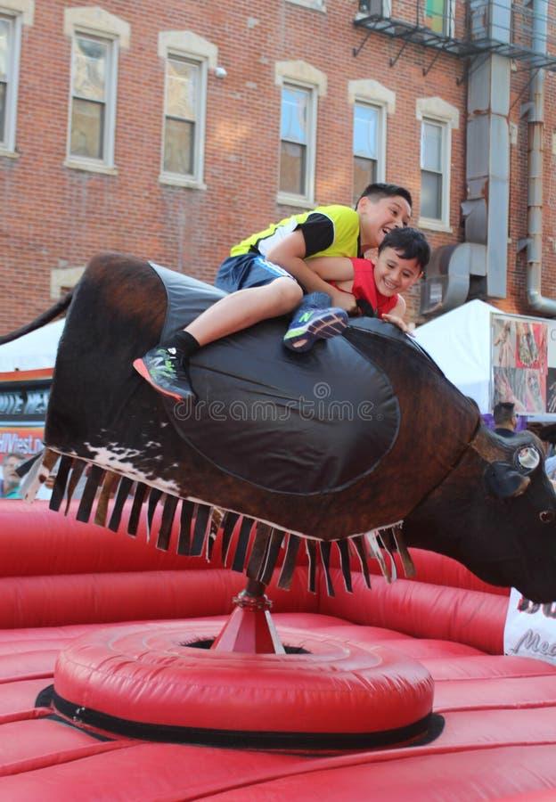 Le rider pojkar en mekanisk tjur på en mexicansk gatafestival i Chicago arkivbild