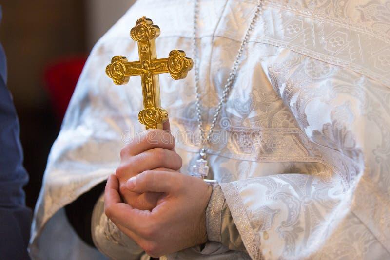 Le rite du baptême - la croix d'or est dans les mains orthodoxes de prêtre photographie stock