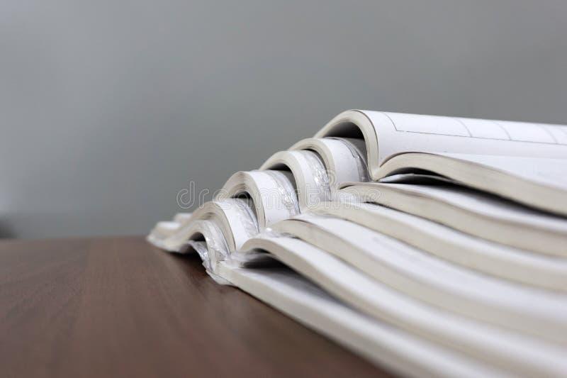 Le riviste aperte si trovano sopra a vicenda su una tavola marrone, documenti sono primo piano impilato immagine stock libera da diritti
