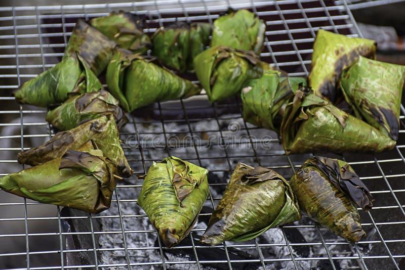 Le riz collant enveloppé dans des feuilles de banane, rôties sur le gril est un aliment populaire en Thaïlande photo stock