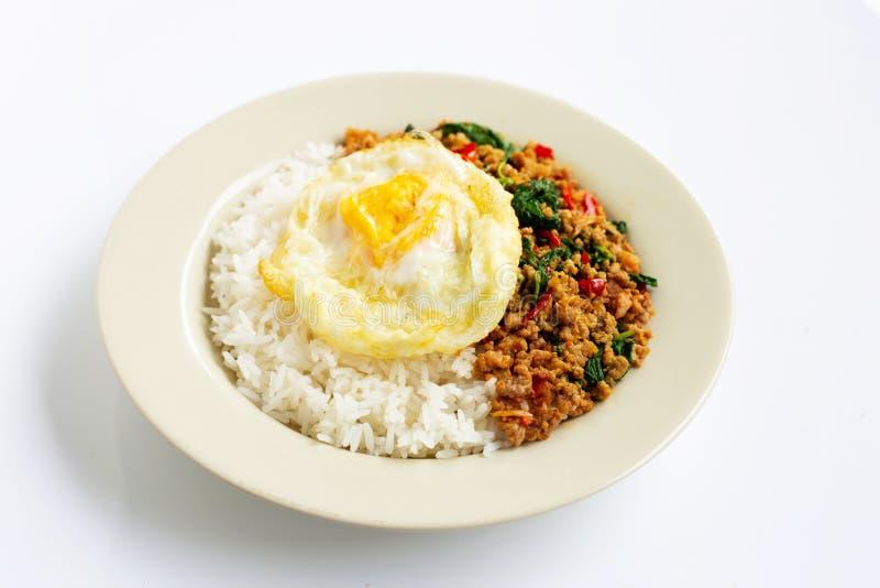 Le riz a complété avec du porc fait sauter à feu vif avec le basilic et l'oeuf au plat saints photos libres de droits