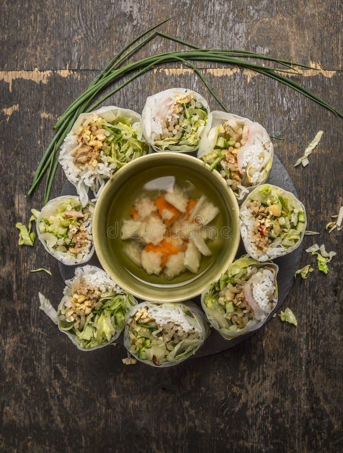 Le riz coupé en tranches roule le cercle rayé autour d'un bol de potage aux légumes sur la vue supérieure de fond en bois photo stock