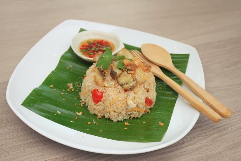 Le riz frit avec le tilapia a fait frire le service sur des feuilles de banane Mettez dessus un plat blanc photographie stock