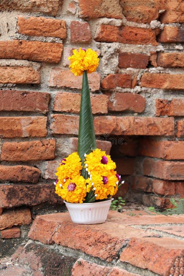 Le riz offrant de la feuille de banane et le souci jaune fleurissent sur la brique image libre de droits