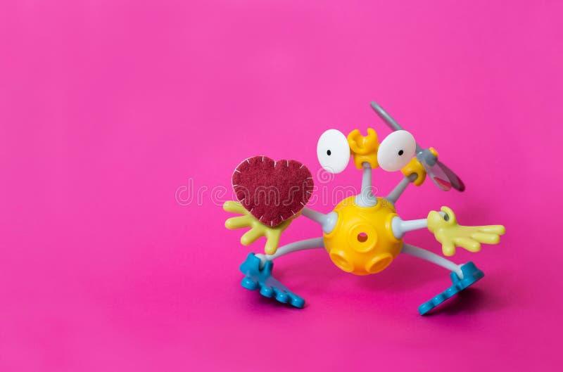 Le robot tient un coeur Le robot donne le coeur Fond rose Jour du `s de Valentine photos stock
