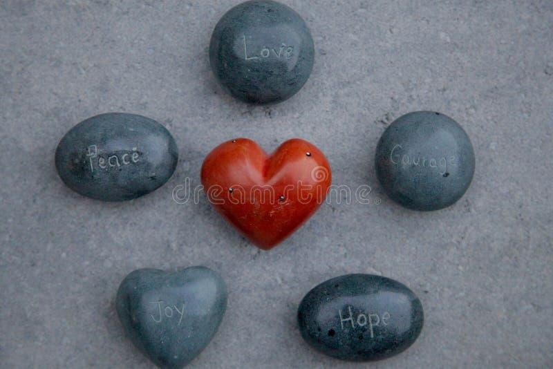 Le rocce incise con le parole amano, pace, coraggio, speranza, la gioia che circonda un cuore rosso fotografie stock libere da diritti